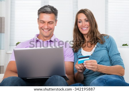 Mature Happy Couple Shopping Online On Laptop With Credit Card At Home