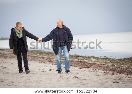 mature happy couple walking on beach in autumn lifestyle healthy - stock photo