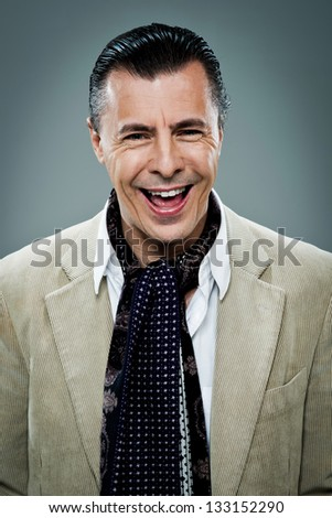 Mature Happy Man Laughing Over a Grey Background