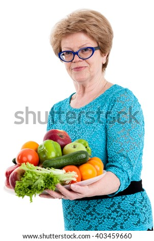 Mature happy woman holding a tray with fruits and vegetables in hands, isolated white background - stock photo