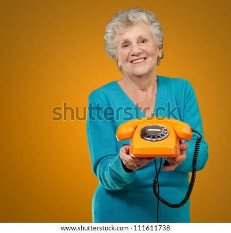 Mature Happy Woman Holding Telephone On Coloured Background - stock photo