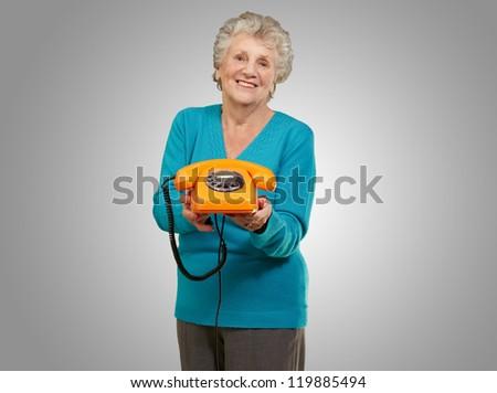 Mature Happy Woman Holding Telephone On Grey Background - stock photo