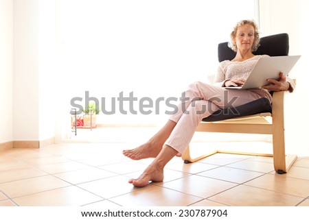 Mature healthy successful professional woman sitting and relaxing in an armchair at home using a laptop computer for internet on line recreational leisure, interior. Technology and lifestyle at home.