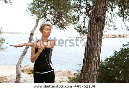 Mature healthy woman stretching her arms, exercising in coastal nature destination with trees, rocks and the sea, outdoors. Wellness and fitness lifestyle, senior woman athlete discipline and effort. - stock photo