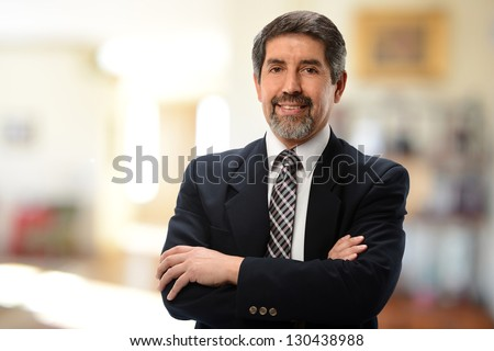 Mature Hispanic Businessman with arms crossed isolated on a white background - stock photo