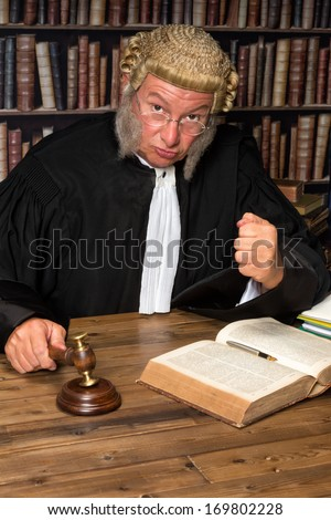 Mature judge with authentic court wig holding a gavel in court - stock photo