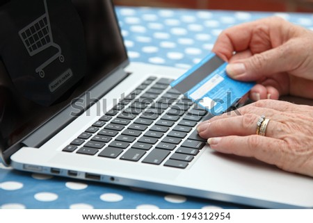 Mature lady at home on line shopping on her laptop and her credit card. - stock photo