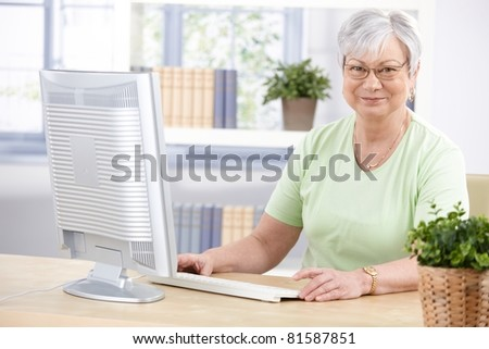 Mature lady browsing internet at home, smiling.? - stock photo