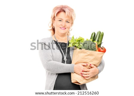 Mature lady holding a bag full of groceries isolated on white background