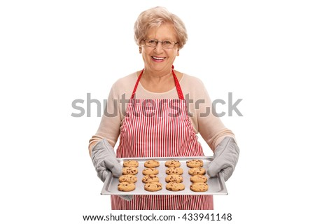 Mature lady holding a tray with homemade chocolate chip cookies isolated on white background - stock photo