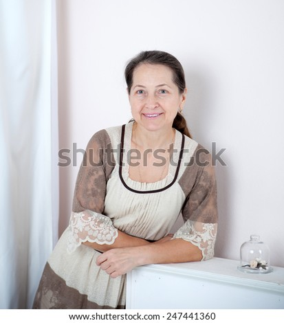 Mature lady in   elegant dress   near  white fireplace. - stock photo