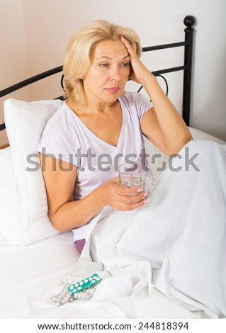 mature lady with pills in bed - stock photo
