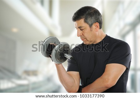 Mature latin man working out with weights indoors