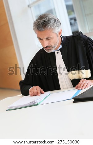 Mature lawyer working on judgement report - stock photo
