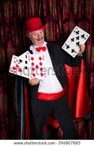 Mature magician on stage performing a magic trick with cards