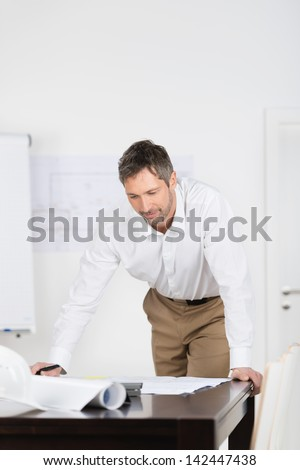 Mature male architect looking at blueprint at desk in office - stock photo