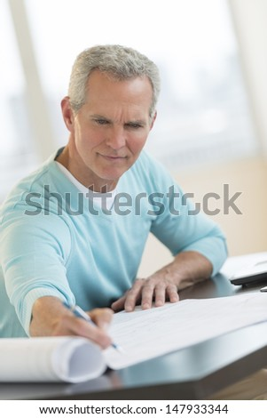 Mature male architect writing on blueprint at desk in office - stock photo