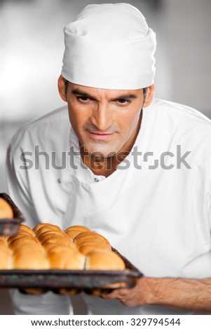 Mature male baker looking at freshly baked breads in baking tray at bakery - stock photo