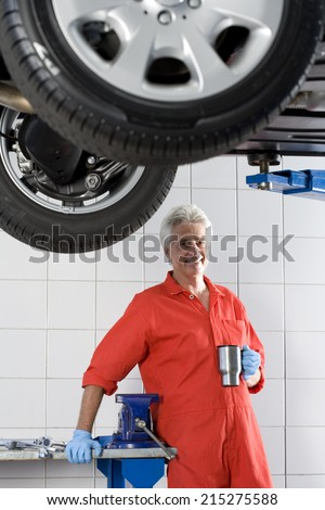 Mature male car mechanic, in red overalls and protective gloves, taking tea break near hydraulic platform in auto repair shop, smiling, portrait - stock photo