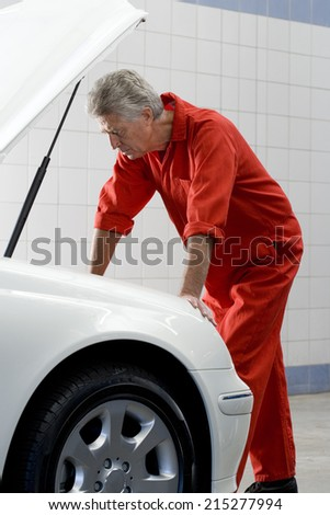 Mature male car mechanic, in red overalls, looking at car engine in auto repair shop, side view - stock photo