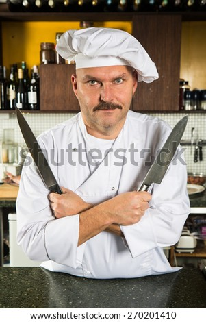 Mature male chef holding two knives in his hands - stock photo