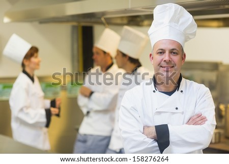 Mature male chef posing proudly in a kitchen with crossed arms and cooks in the background