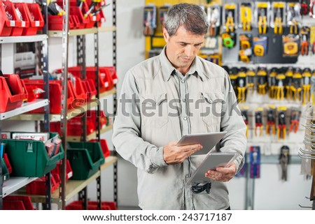 Mature male customer analyzing product through digital tablet in hardware store