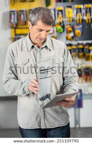 Mature male customer scanning product through digital tablet in hardware store - stock photo