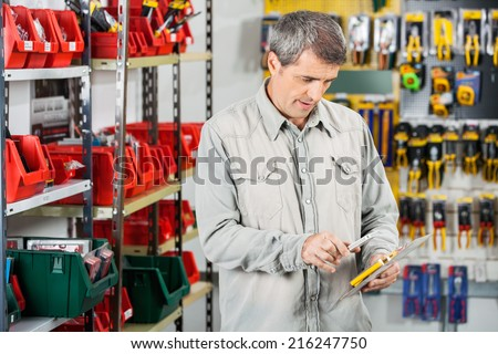Mature male customer scanning tool packet through smartphone in hardware store - stock photo