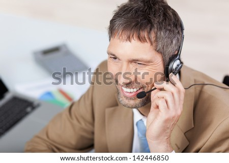 Mature male customer service executive conversing on headset at desk in office - stock photo