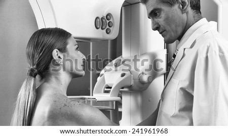Mature male doctor assisting young patient during mammography. - stock photo