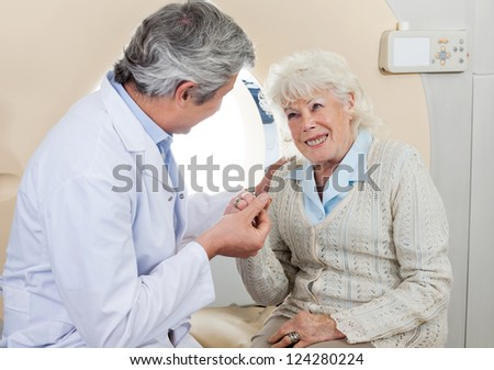 Mature male doctor comforting senior female patient before CT scan test - stock photo
