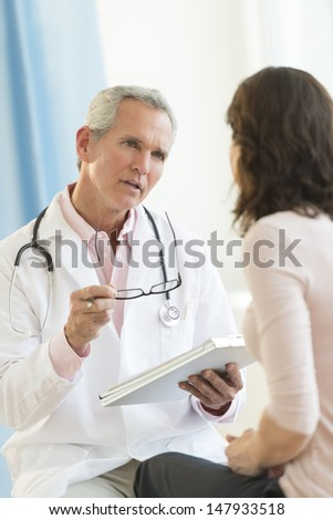 Mature male doctor communicating with female patient in hospital