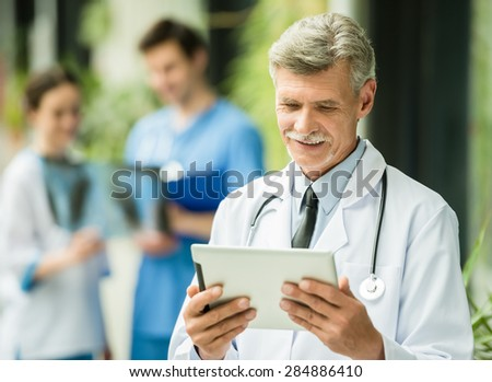 Mature male doctor looking at digital tablet. Healthcare and medicine concept. - stock photo