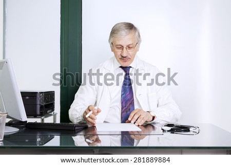 mature male doctor sitting at desk in doctor's room