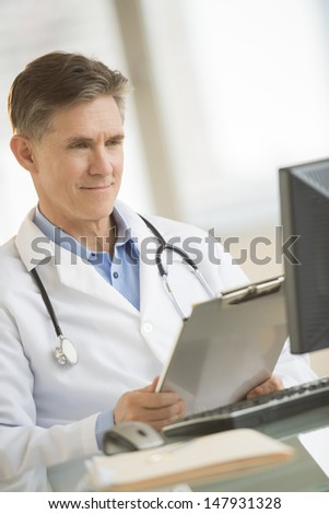 Mature male doctor smiling while looking at computer in clinic