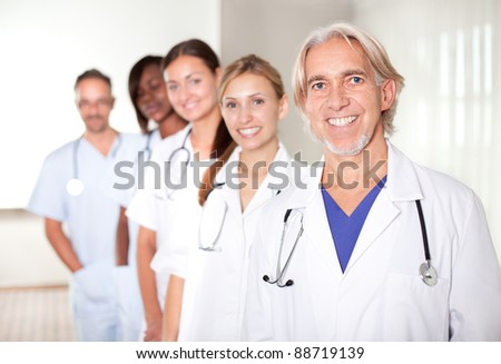 Mature male doctor with his team of colleagues out of focus behind him. - stock photo