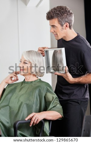 Mature male hairstylist showing finished haircut to senior woman at salon