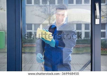 Mature male janitor cleaning glass with rag