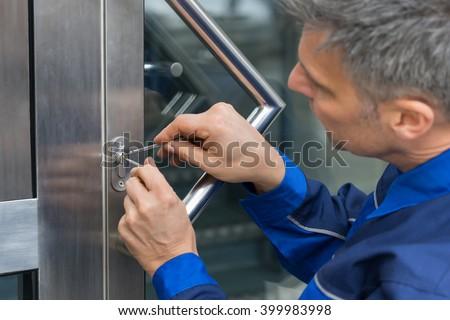 Mature Male Lockpicker Fixing Door Handle At Home - stock photo