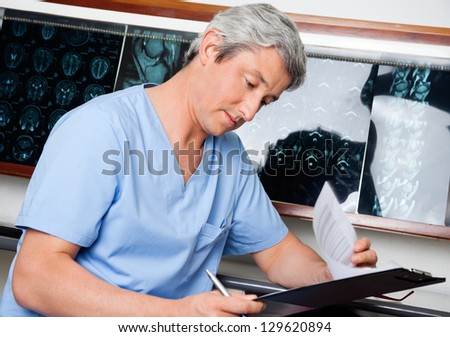Mature male medical professional in uniform going through document at clinic - stock photo