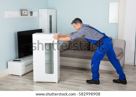 mature male mover placing furniture in living room at home