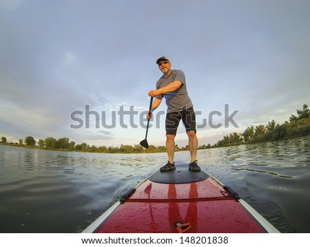 mature male paddler enjoying workout on stand up paddleboard (SUP), calm lake in Colorado, summer - stock photo