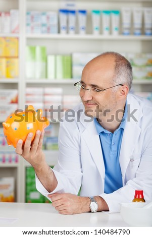 Mature male pharmacist holding piggybank while leaning on pharmacy counter - stock photo