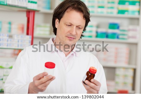 Mature male pharmacist holding pill bottles in pharmacy - stock photo