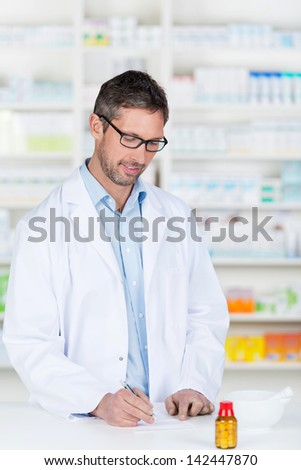 Mature male pharmacist writing prescription on paper at pharmacy counter - stock photo