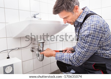 Mature Male Plumber Fitting Sink Pipe In Bathroom - stock photo