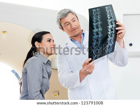 Mature male radiologist and young female patient looking at x-ray report