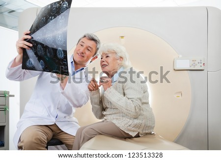 Mature male radiologist explaining CT Scan to an elderly female patient - stock photo