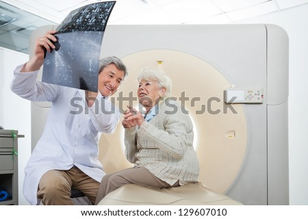 Mature male radiologist with an elderly female patient looking at CT scan results - stock photo